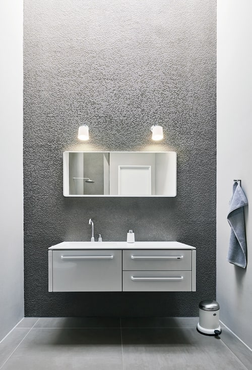 Minimalistiskt badrum i silver och vitt.