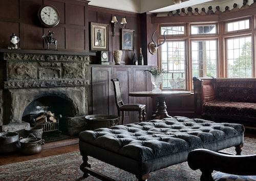 """Hela läsrummet, The study, är inklätt med mörkbetsad panel. Den sotiga eldstaden är huggen ur sten och fönsterrutorna mot terrassen är blyinfattade. Inredningen är därefter: sammet, persisk matta och möbler i barock- och nyrenässansstil. Det enda vita är urtavlorna, annars skulle inte visarna synas. """"Det här är mitt favoritrum i huset. Formellt och maskulint, men nyckfullt och romantiskt på samma gång."""""""