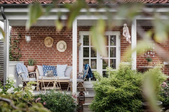 Lätta rottingmöbler fyllda med textilier, blå toner blir extra vackra mot tegelväggen, en stråhatt eller två och utelivet är komplett. Bambu och rotting trivs bäst i skuggan. En plats under tak ger skydd mot både regnstänk och sol.
