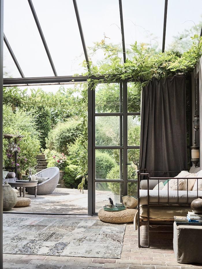 Skjutdörrar sparar plats och är en smidig lösning för det inglasade uterummet. Öppna precis så mycket du vill för frisk luft men slipp en dörr som står och slår i vinddraget. Utsikt mot både trädgård och molntussar. Att förlänga säsongen med ett inglasat rum eller orangeri, ja, det är drömmen för många! Rotting i stort och smått liksom textilier ger en mjuk och naturlig känsla.