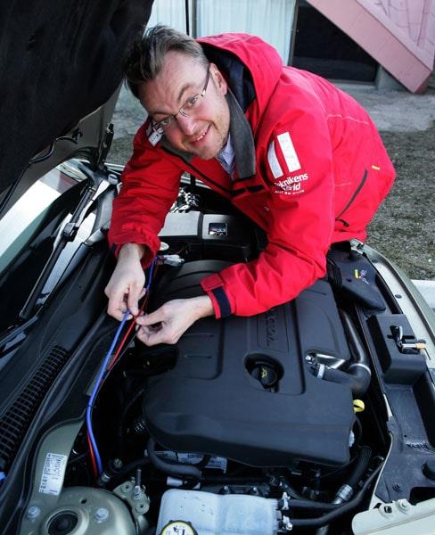 Hans Hedberg visar upp kablarna som går till mc-batteriet som servar bilen vid stopp.