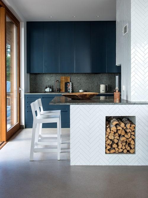 Kökets mörka toner av blått och grått (bänkskivor i öländsk kalksten och golv av polerad betong) kontrasterar mot vitt fiskbensmönstrat kakel från Höganäs och naturträ. Köket är från Nordiska kök och stolarna från Gärsnäs fabriksbutik på Österlen.