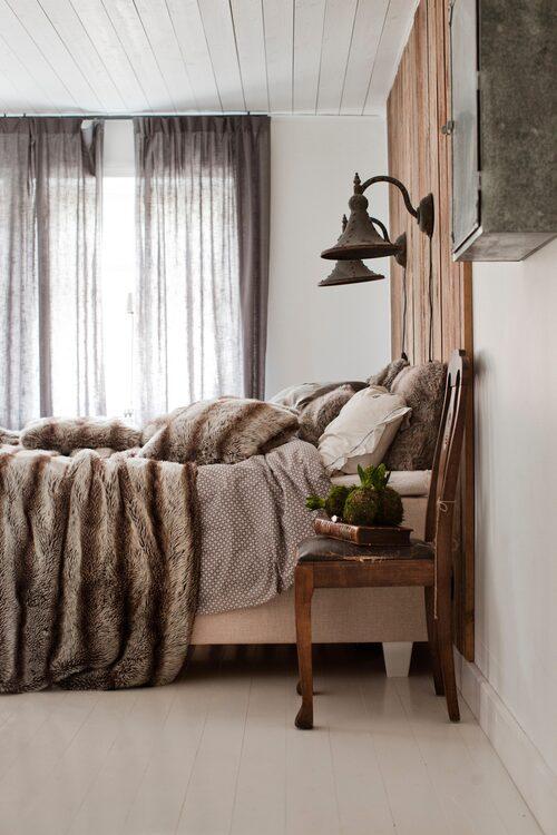 I Carinas och Baltzars sovrum har sänggaveln ersatts med en vägg av plankor. Överkast, EB:s country design, och lampor, Hjärterum. Stolen var ett antikfynd.