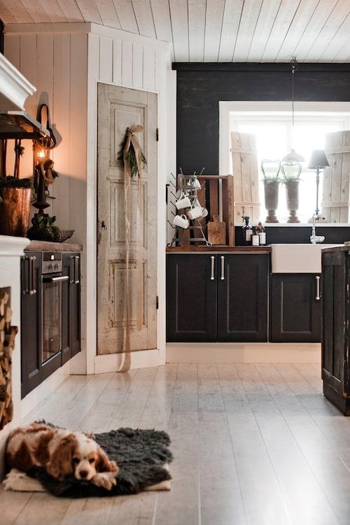 I köket är adventskänslan på topp med mycket grönt och tända ljus. Den svarta färgen tillsammans med naturtoner gör köket ombonat.