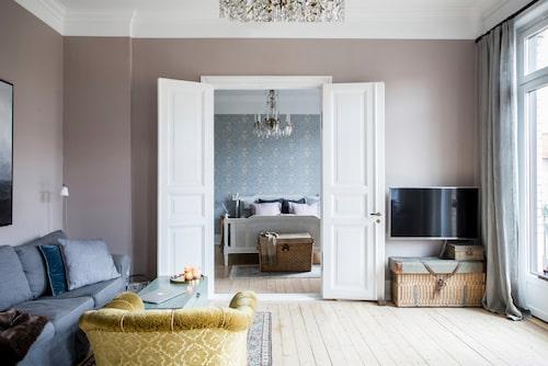 Kristallkronorna är arvegods. Linne och sammet samsas fint med vitlaserade trägolv. Soffa, Ikea.