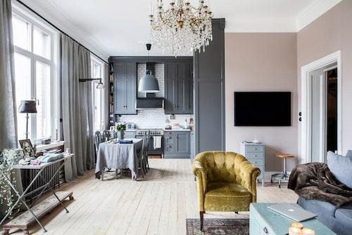 Det grå köket möter vardagsrummets varmt rosa väggar. Många av de personliga detaljerna kommer från franska och svenska auktioner och loppisar. Den svarta tavlan är målad av konstnären och vännen Bo Hultén. Tenngrå gjutjärnselement från Gamla mejeriet.