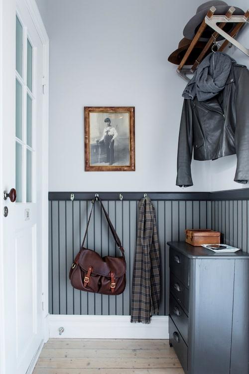 Hallens väggar har fått en markerad bröstlist och tapet från Ralph Lauren, Engelska tapetmagasinet. Fotot från 1908 på pojken med byxorna fastknäppta i skjortan hittades i Frankrike. Väska Brady, England.
