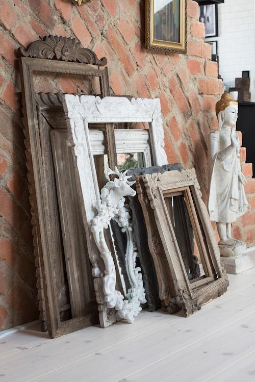 Den gamla murstocken är en naturlig rumsavdelare mellan kök och vardagsrum. En samling ramar i olika storlekar och träslag blir ett vackert arrangemang.