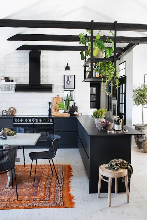 Köket kommer från italienska Arrital och bänkskivan är i ett material som heter Dekton och tillverkas i Spanien. Kakel Paris från Kakelspecialisten. Från takbjälkarna hänger ett specialbeställt barskåp.