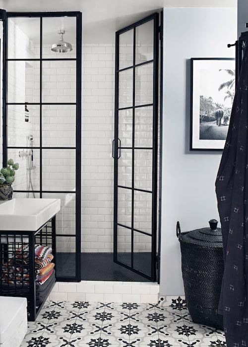 """De specialbeställda dörrarna till duschutrymmet följer samma formspråk som fönstren och terrassdörrarna. På väggarna sitter samma kakel som i köket, och golvet är likadant som det på terrassen, Cementine black & white, Kakelspecialisten. """"Om man håller sig till ett fåtal material bildar inredningen en helhet"""", säger Yvonne."""