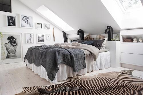Vitpigmenterade trägolv ger en varm ton åt sovrummet. Upp mot taknocken har ett fönster tagits upp för att få dagsljus i badrummet. Platsbyggda byråer tar vara på det svårmöblerade utrymmet under snedtaket. Sängkläder från Himla och fotokonst, Love warriors.