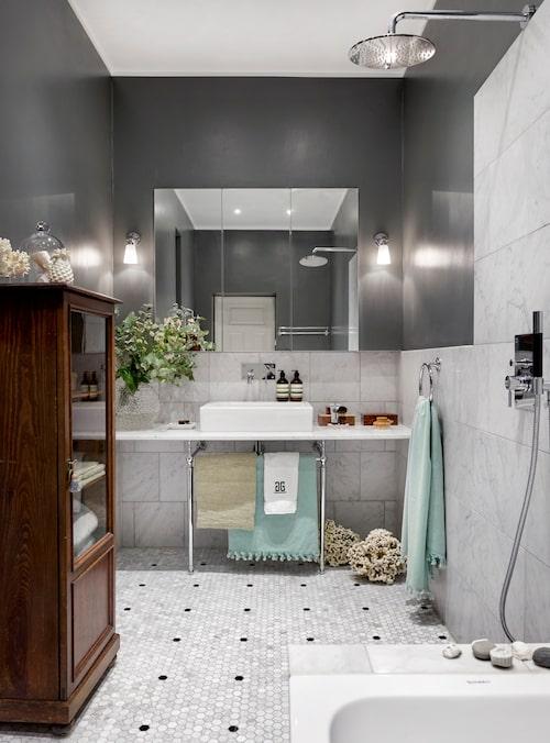 Övre delen av badrumsväggen är målad med våtrumsfärg Modernism grå/32, Flügger. På nedre delen, carraramarmor 30x30cm satt i halvförband. På golvet: Hexagonformad mosaik i bricmate-marmor. Handfat Duravit Vero med blandare Tapwell Box 006. Kromställning Burlington och handduksring i krom, båda från Sekelskifte. Dusch, Tapwell Box 7200.