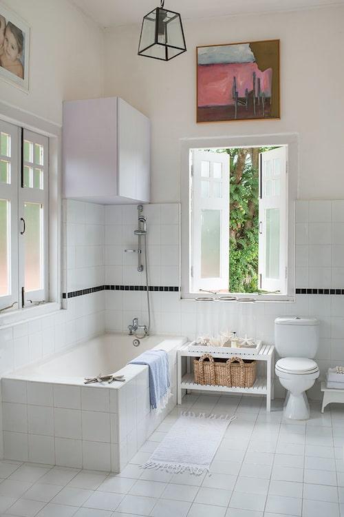 Ett av badrummen, klätt helt i vitt kakel, med grönskan utanför som en tavla på väggen.
