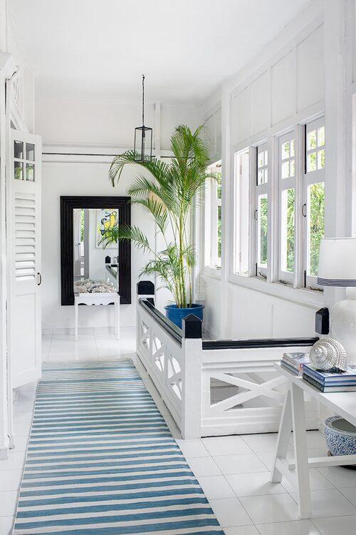 Den övre passagen med spegel och vitmålat golv som ytterligare öppnar upp, medan en blåvitrandig bomullsmatta accentuerar det långsträckta rummet. På bordet syns en dekorationssnäcka i metall.