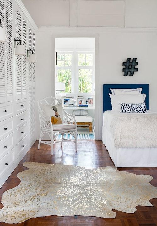 Döttrarnas sovrum med guldskimrande koskinn på golvet, en bambuinspirerad karmstol och en hashtag-lampa ovanför sängen. Bakom skymtar passagen mot bakre delen av huset.