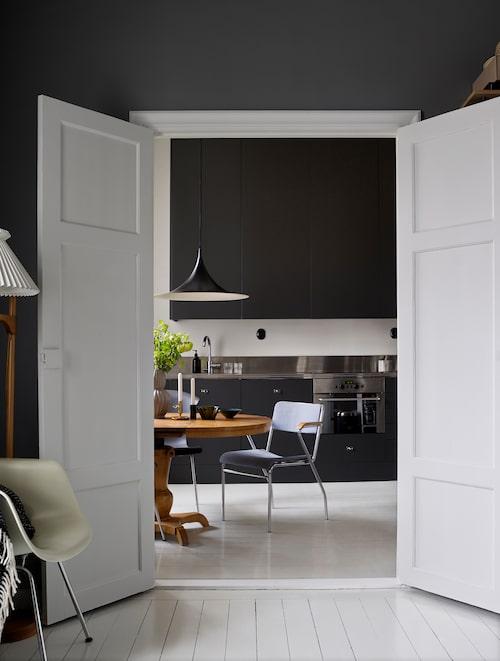 Öppningen med dubbeldörrar mellan kök och vardagsrum skapar härlig kontakt mellan rummen. Svart kök från Ikea.