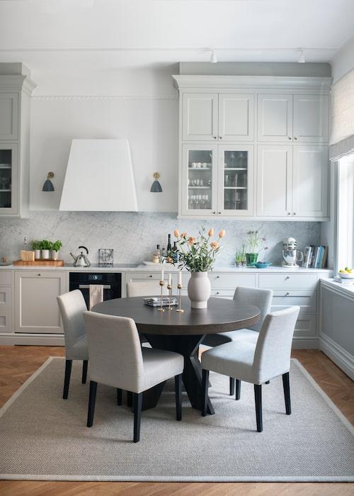 Köket är platsbyggt av möbelsnickare. Matbordet går enkelt att förlänga med iläggsskivor. Matbordsstolarna  är utplacerade på olika platser i hemmet, till exempel vid skrivbordet. Bord, stolar och matta från Slettvoll.