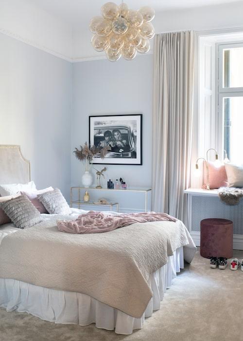 Yngsta dottern Filippas rum med matchande gardiner och heltäckningsmatta från Slettvoll. Taklampa Amber från By Rydéns, kuddar och pläd samt sidobord från Frejas boning. Lampan i fönstret är från Globen lighting och den rosa puffen är köpt på Åhléns.