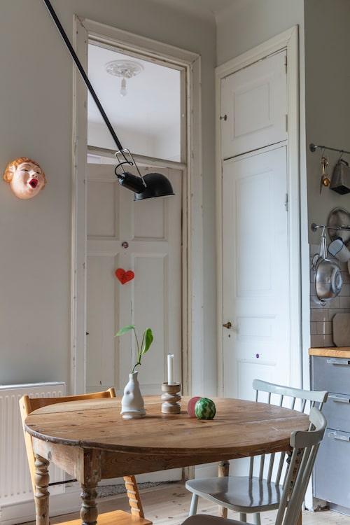 I det mysiga köket står ett bord som köptes på Blocket av en kille som hittat det på tippen och fixat till det. Lampan är Flos 265, inköpt i Italien. Vas av Lisa Hartwig Ericson och gumman på väggen är en toapappershållare från Indonesien.