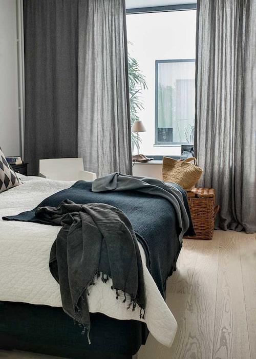 Ett sovrum i vitt och lugna grå toner. Långa gardiner i tyg från Astrid – sydda av Ia liksom övriga gardiner i hemmet. Fåtölj, Philippe Starck, och svart, tunn pläd, Olsson & Jensen.