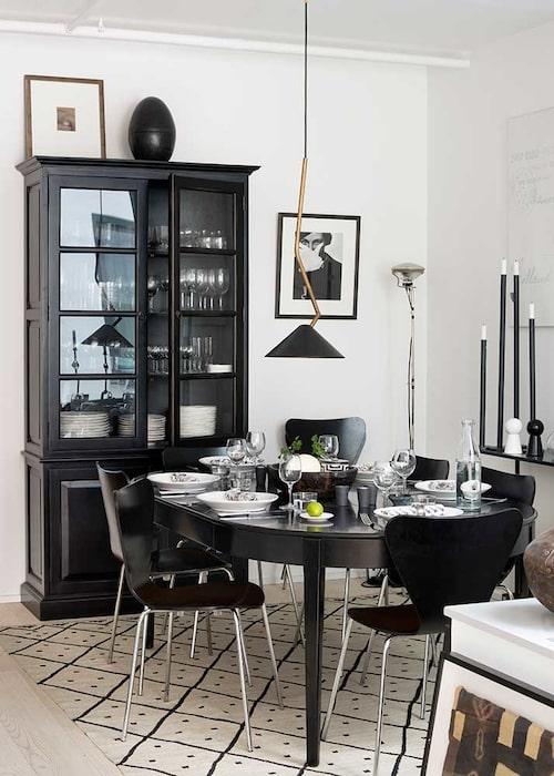 Klassiska Sjuanstolar runt det svarta matbordet. Vitrinskåp, PB home, på golvet marockansk matta som binder ihop gruppen. Pendellampa, Oscar & Clothilde. Rörljusstakarna t h från Röshults.