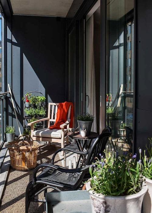 På balkongen – med skjutfönster mot gatan – tillbringar Ia gärna tid. Trästolen Terrazza är köpt på Mallorca. Bredvid den en hylla för örter och växter. Svart korgstol, Granit.