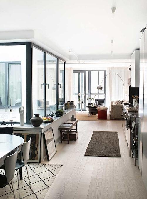 Lägenheten ligger runt ett atrium i den forna chokladfabriken på Kungsholmen, och har en urban inredningsstil i beige, svart och orange i naturliga materialval. Svarta dörr- och fönsterbågar skänker en maskulin känsla. På fönsterbänken t v står prydnader Ia älskar.