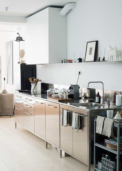 Ett välplanerat, blänkande rostfritt kök smälter in i stilen. Platsbyggt med spis, arbetsbänk och ho i rad.