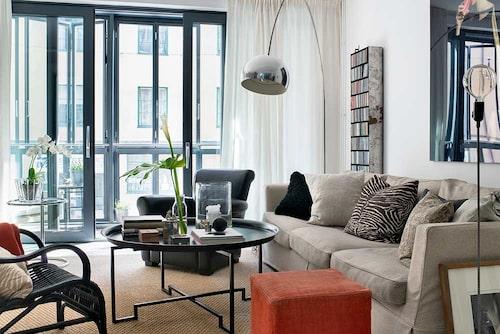 Från vardagsrummet kliver man ut på balkongen. Långa, svepande gardiner sydda av tyg från Astrid. Beige soffa, R.o.o.m, skinnfåtölj, Ralph Lauren, korgstol, Granit. Svart soffbord, Per Öberg. Lyser upp gör den klassiska Castiglionilampan på marmorfot, från Flos. I förgrunden lampa på styv lampsladd, Designhouse Stockholm.