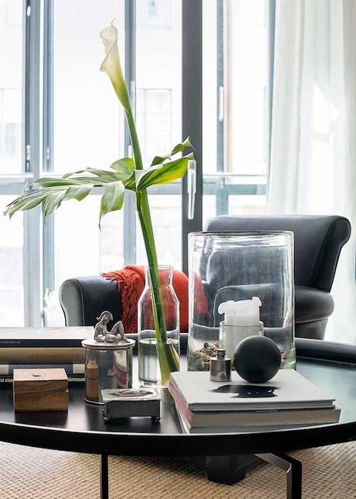 Lägenheten kunde ha blivit mörk men de stora fönsterpartierna släpper in ljuset. På soffbordet av Per Öberg syns reseminnen, böcker och kära ting.