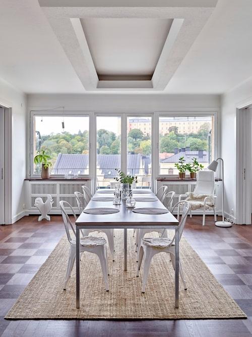 De stora fönstren gör den magnifika utsikten allestädes närvarande – inte undra på att gäster på besök gärna blir sittande här länge, länge. Ramen i taket är original och hade från början en rad glödlampor som nu bytts ut mot en led-slinga. Betongbord från MBJ design, stolar, Tolix.