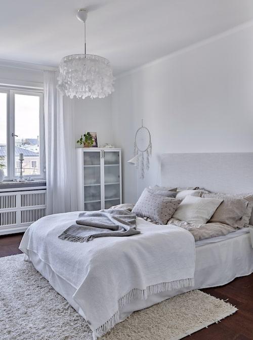 Parets sovrum har ett lugnt läge åt öster där man kan njuta av morgonsolen på balkongen. Sänggavel från Sweef, och bäddning från Hemtex med kuddar från House of Rym och Ikea. Vitrinskåp Azzaro från Voice där lakanen förvaras. Taklampa Fly från Catarina Larsson.