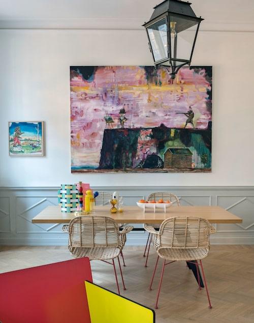 Vardagsrummet går över i matsalen med bord av Prouvé och rottingstolar med metallben från Afroart. På bordet en skål från Fort standard, en designduo i New York. Ljusstake, Seletti, och timglas, Hay. Den stora målningen av Olle Schmidt och den mindre av Scooter LaForge. I taket en fransk gatlykta.