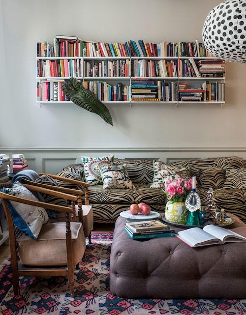 """Tv- och läsrum med många mjuka sitsar. Tygtapeten är från Ralph Lauren i skjortblå färg. Karm-stolar från Bukowskis och persisk matta, 1940-tal. """"Det är bra med en matta i ett större rum, den samlar upp mycket damm som annars skulle virvla runt på kala ytor."""" Kuddarna i vintagesoffan är från Pierre Frey i mönstret Montana."""