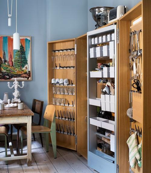 """Färgen på väggarna är Morning blue nr32 från Mylands, som Johan säljer i sin butik Fablab. """"Färgen har glans 3 och en marmorputs som gör att den tål tekniskt slitage i kök och badrum."""" Skåpet är från Bulthaup, ur serien B2, """"inspirerat av hantverkare, att man enkelt ska komma åt sina verktyg och redskap"""". Målning av vännen och konstnären Scooter LaForge. Ljust mintgrön taklampa från Studio WM. Kandelaber med clownhuvud från Seletti. """"Också ett märke jag säljer i butiken."""""""