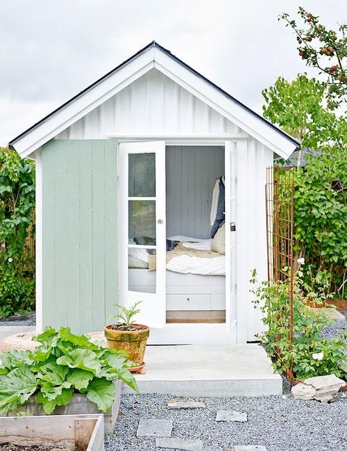 """Mitt i trädgården står en liten """"sovbod"""" som paret byggt på gammalt vis. Gamla fönster återanvändes och byggdes om till pardörrar."""