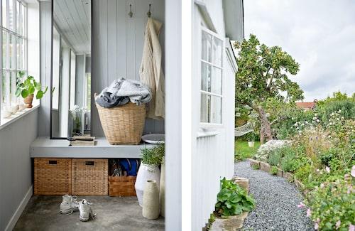 """På hallgolvet står flera stora krukor av stengods, som Elin själv tillverkat. Korgar och spegel från Ikea. På vårkanten slänger paret ut blomfrön lite här och där för att trädgården inte ska bli alltför """"organiserad""""."""