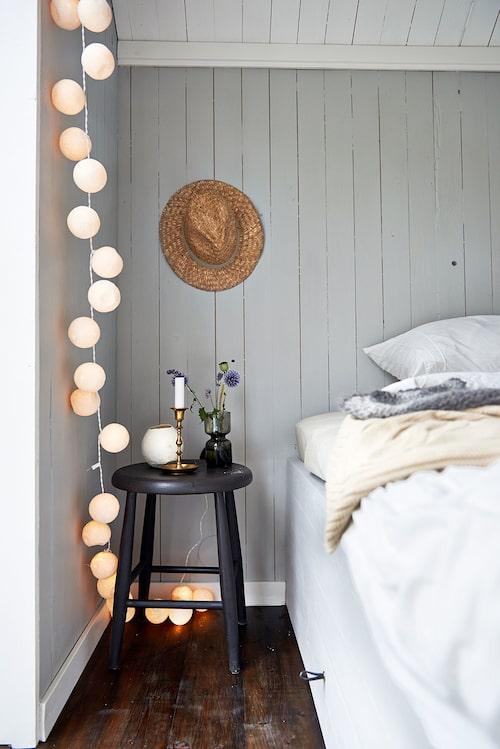 Sängramen i sovboden är platsbyggd med smart förvaringslåda. Pallen är ett ommålat loppisfynd.