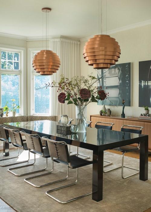 Mondän matsal. Ovanför bordet specialbeställda lampor från Porada, även skåp och bord därifrån. Stolarna är köpta i Italien och mattan kommer från Nordiska hem. Framme vid burspråket en platsbyggd soffa, klädd i tyg från Ralph Lauren home.