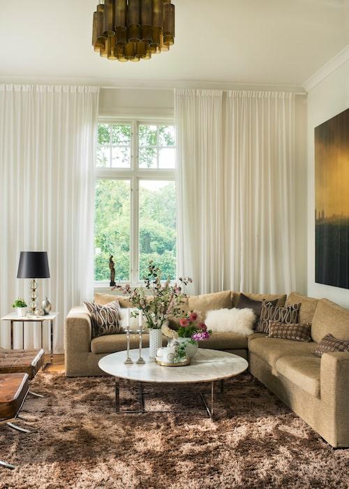 Gardiner från golv till tak ger en ombonad känsla. Taklampan är köpt på auktion, soffa från Minotti, soffbord från Porada, mattan är köpt via en god vän, men av okänt märke. Även här i vardagsrummet syns ägarens kärlek till sköna stilleben.