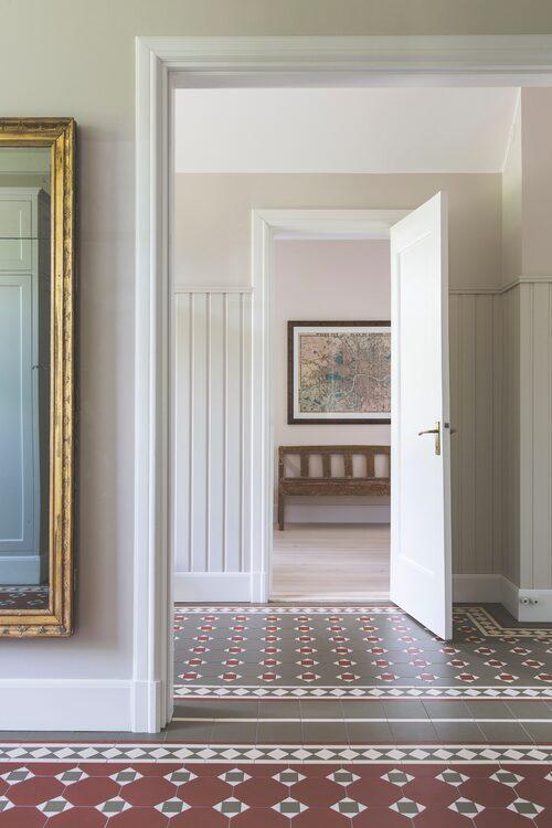 Golvet i farstun och den inre hallen är lagt med engelsk klinker i viktorianska mönsterkombinationer.