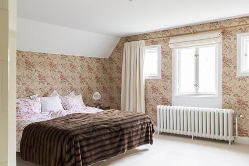 Sovrummet blommar med tapet British rose från amerikanska Wallquest/Tapetorama och lakan från Mille notti. Pläd från Garbo.