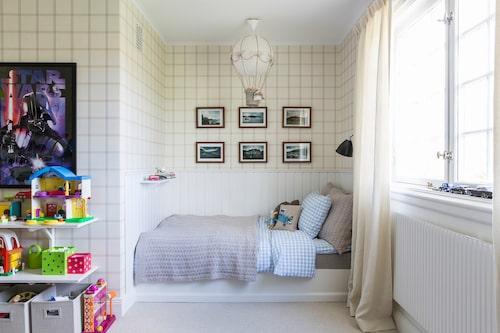 En rutig tapet i rummet där sängen är inbyggd i en panelklädd nisch; här finns plats för liten eller stor att läsa och sova.