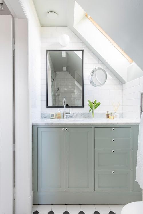 Ett mindre badrum i samma stil. Det kan vara svårt att få platsbyggda lösningar att se ut som originalinredning, men det finns vissa saker som till exempel innanförliggande luckor och lådor som är ett äldre sätt att bygga skåpsinredning.