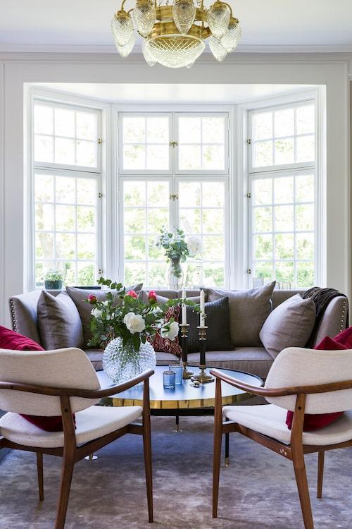 Vardagsrummet är ombonat med en stor bambusilkesmatta som bas, från Glowb. Italienska karmstolar, från Porada, grå soffa Leopold med nitar, Slettvoll, soffbord med mässingsdetaljer, Scherlin, och i taket en nioarmad ringkrona modell 1900, från Karlskrona lampfabrik.