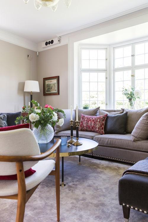 Vardagsrummet med empireljusstakar och Carina Seth Anderssons glasvas, Svenskt tenn, på det runda soffbordet i design av Ulf Scherlin.