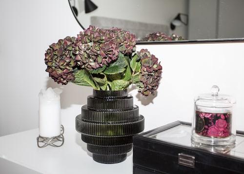 Spegel, vit byrå, och svart vas från Ellos. Ljusstakar från Georg Jensen.