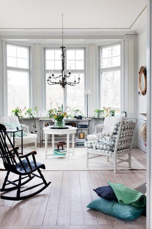 Gripsholmsstolarna passar perfekt i den ljusa inredningen, liksom svärtan i den gamla gungstolen, ett arvegods. Takkronan är nyinköpt på antikmässa och klädd med blad från ett olivträd.