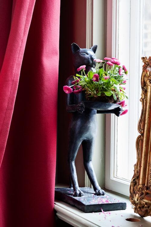Kattskulpturen i fönstret får ibland lyfta fram några blomster. Spegeln med krusidullig guldram är ett arvegods.