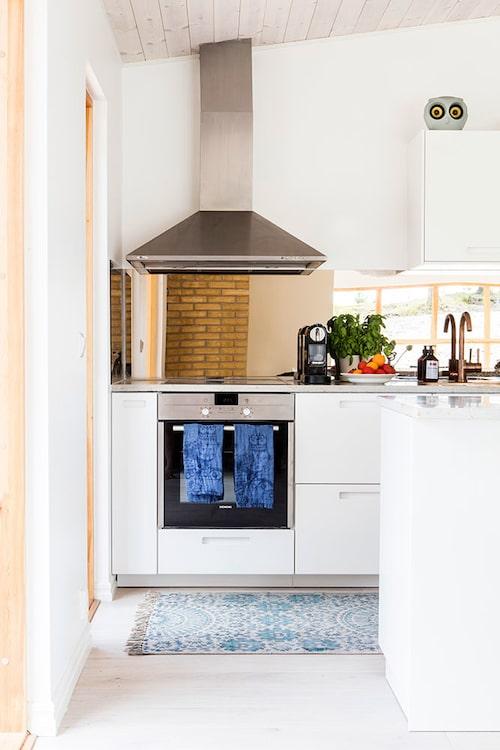 Köksinredningen är från Ikea, vitvarorna från Bosch och kopparkran och ho från Tapwell. Handdukar Taika, Iittala. Stänkskyddet i spegelglas är specialbeställt.